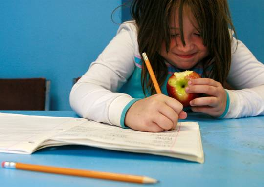 Child doing school work and eating an apple