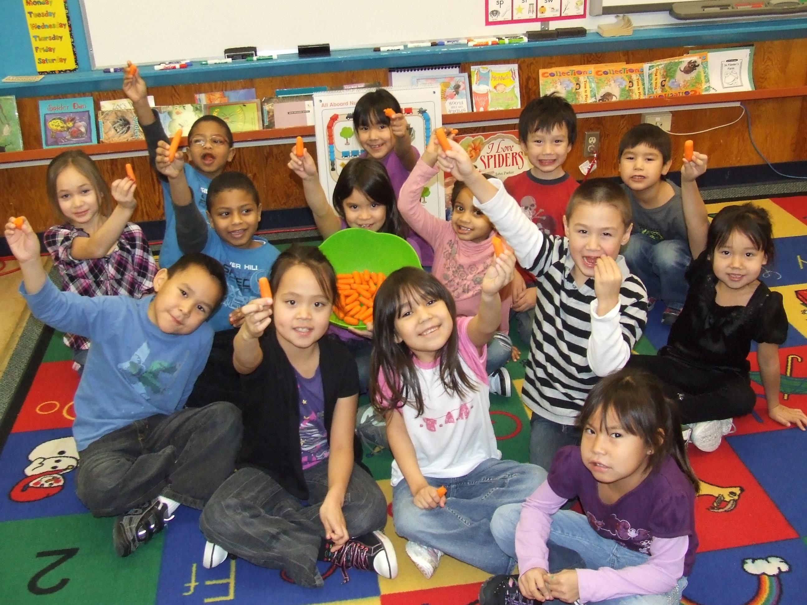 Children in classroom eating carrots