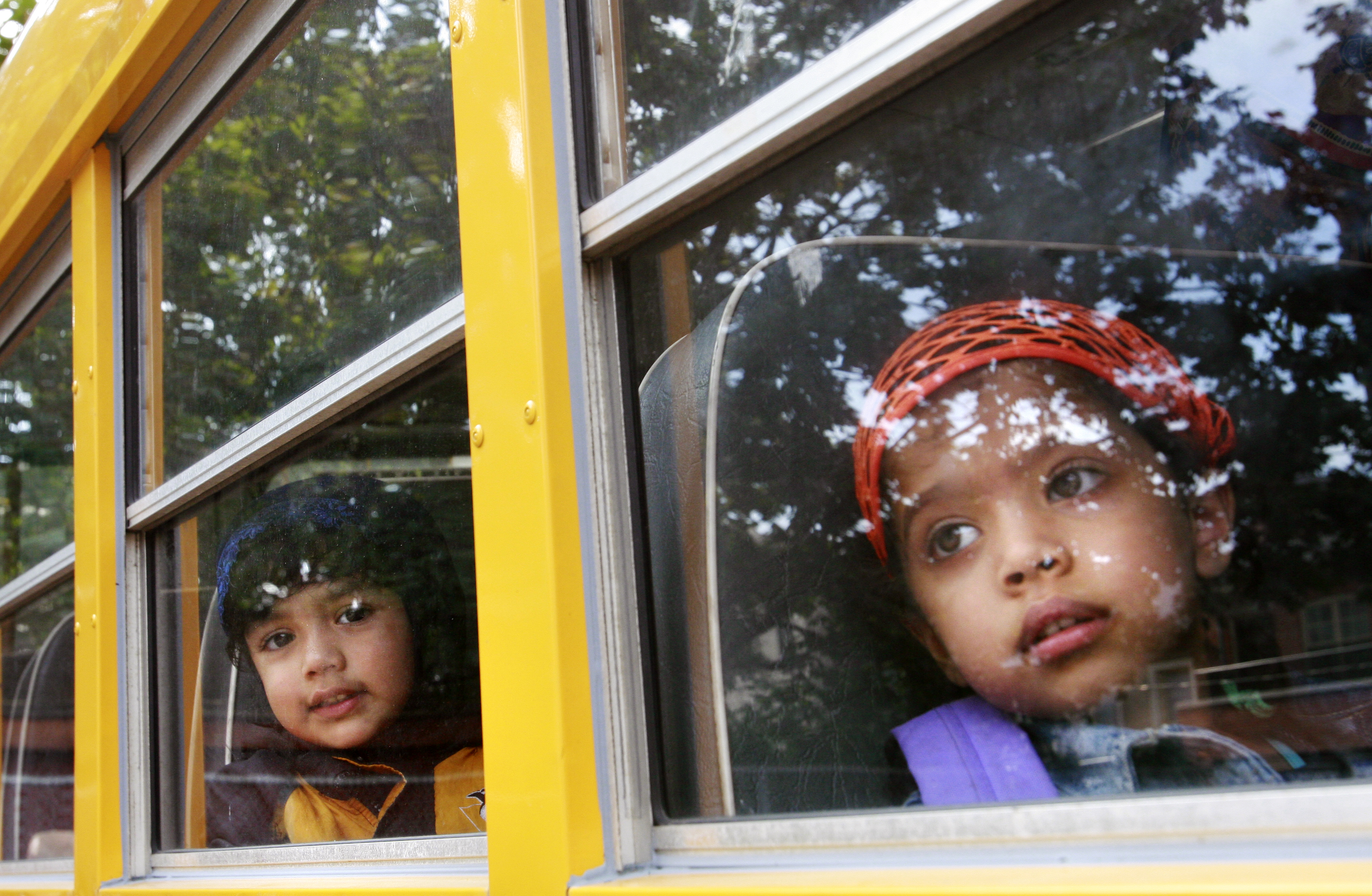 Children looking out of school bus window